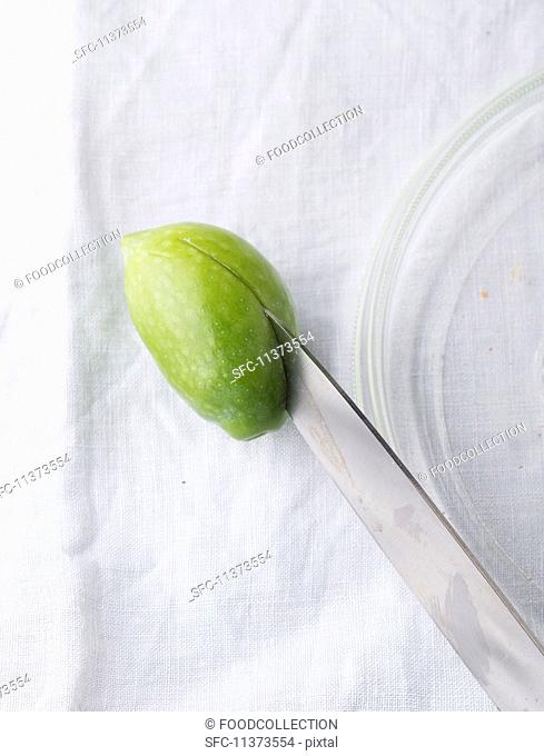 A green olive being halved with a knife (close-up)