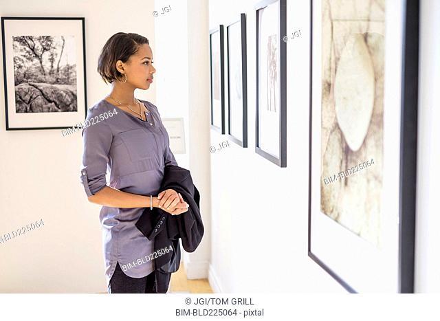 Black woman admiring paintings in art gallery