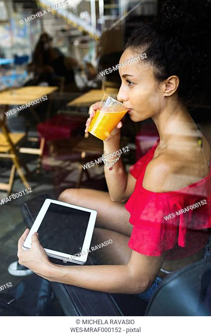 Young woman drinking glass of orange juice in a coffee shop