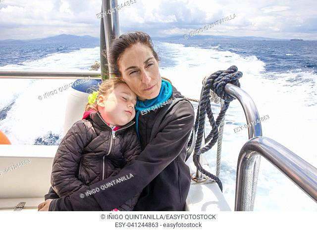 woman hugging her daughter sleeping, four years old girl, sitting on the stern of motor boat sailing in Strait of Gibraltar