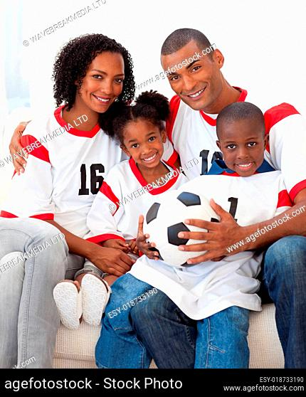 Smiling family holding a soccer ball