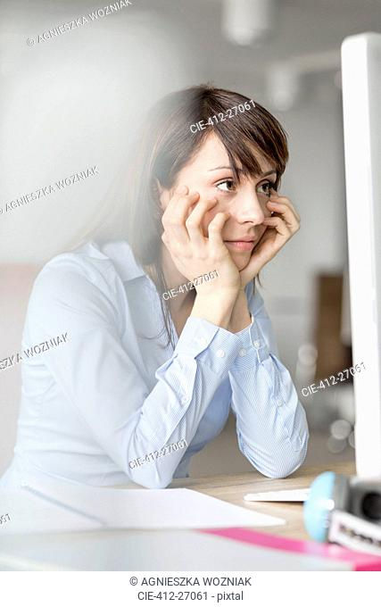 Frustrated brunette businesswoman working at computer in office