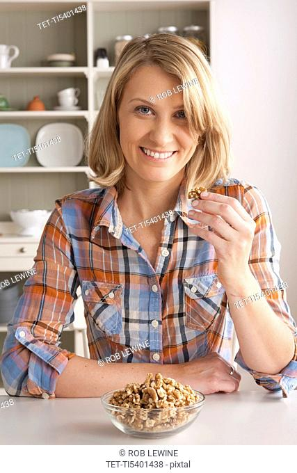 Portrait of mid adult woman with bowl of walnuts