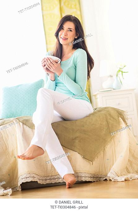 Woman sitting on bed with cup in hand