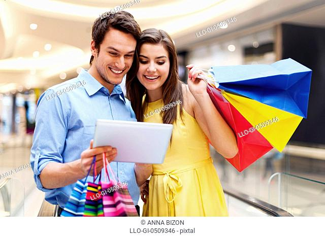 Happy couple using s digital tablet in the shopping mall Debica, Poland