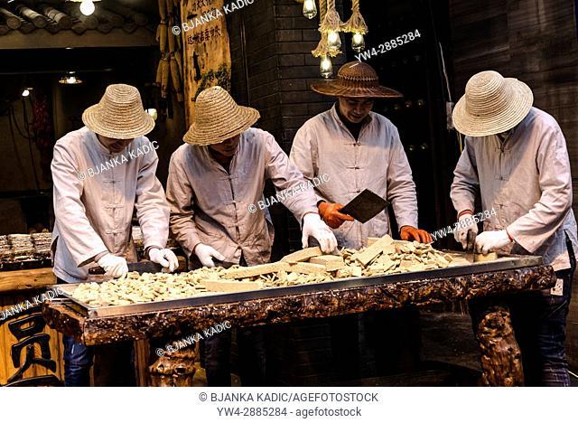 Young men cutting sweets, Street food market, Muslim Quarter, Xi'an, Shaanxi province, China