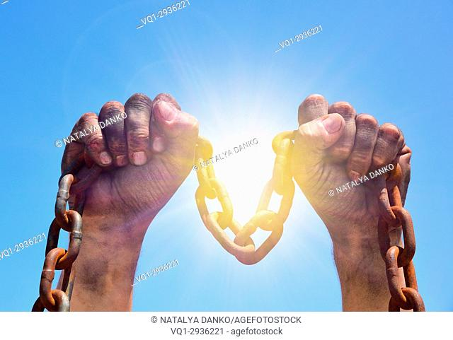 Two male hands are raised upwards with an iron rusty chain against the background of bright sun rays