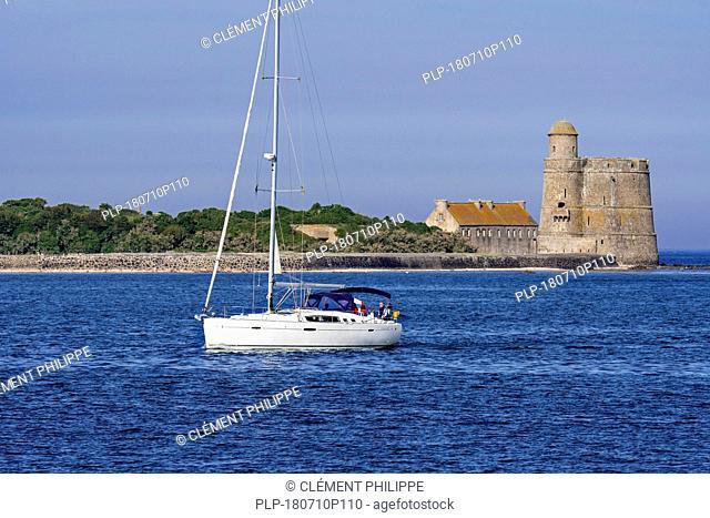 Sailing boat with lowered sails sailing in front of the Tour Vauban at 'île de Tatihou, Saint-Vaast-la-Hougue, Manche department, Normandy, France
