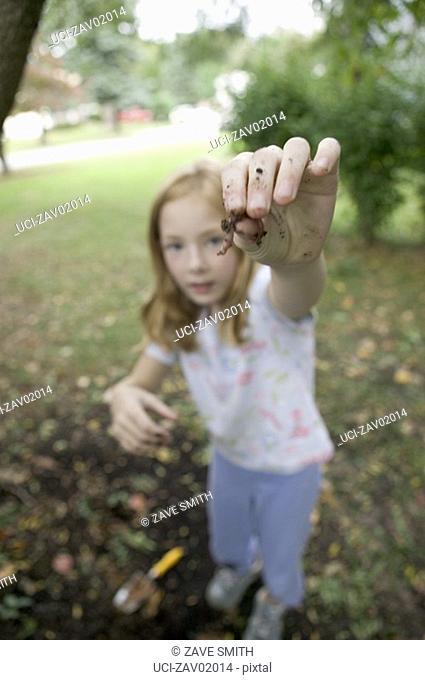Young girl displaying worm in backyard