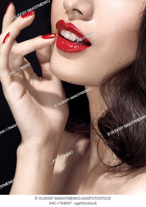 Artistic closeup portrait of closeup of a young woman's mouth with bright red lipstick