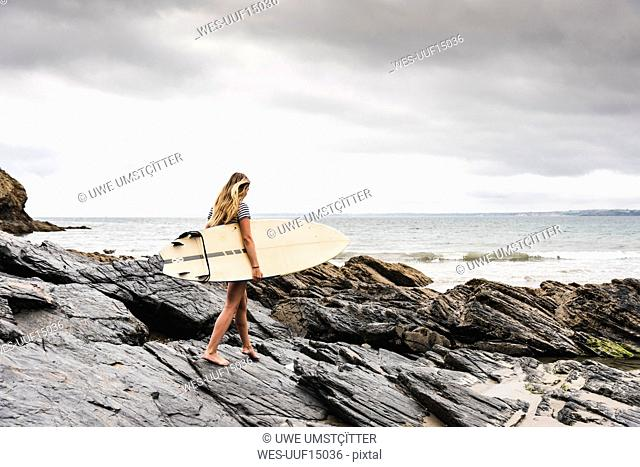 Young woman carrying surfboard on a rocky beach at the sea