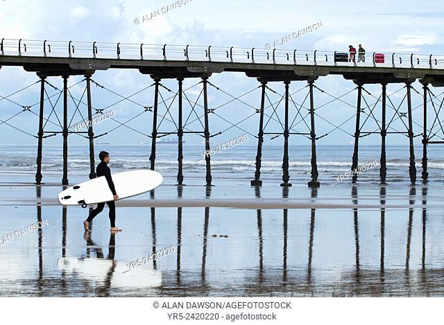 Surfer near Saltburn`s Victorian pier. Saltburn by the sea, North Yorkshire, England, United Kingdom