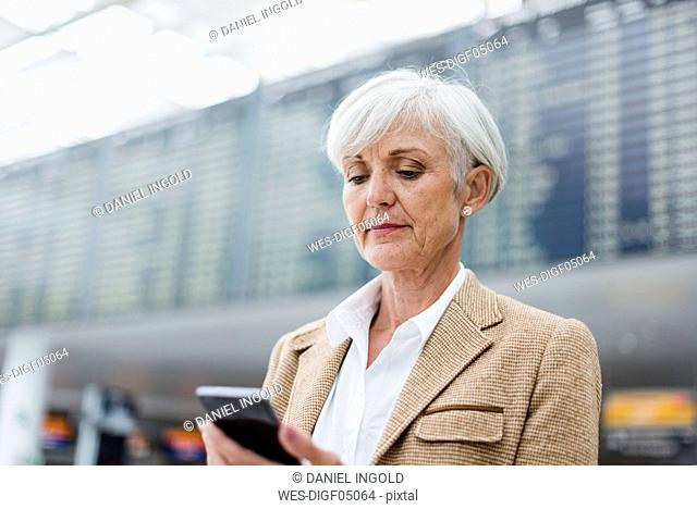 Senior businesswoman using cell phone at the airport