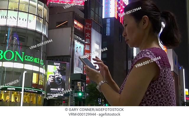 Women using her smart phone at night in Tokyo, Japan