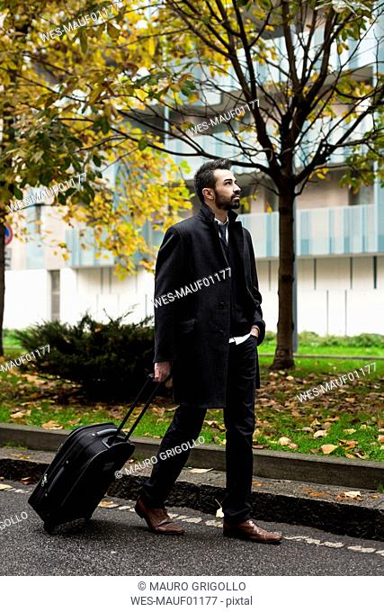 Businessman with suitcase walking in the city