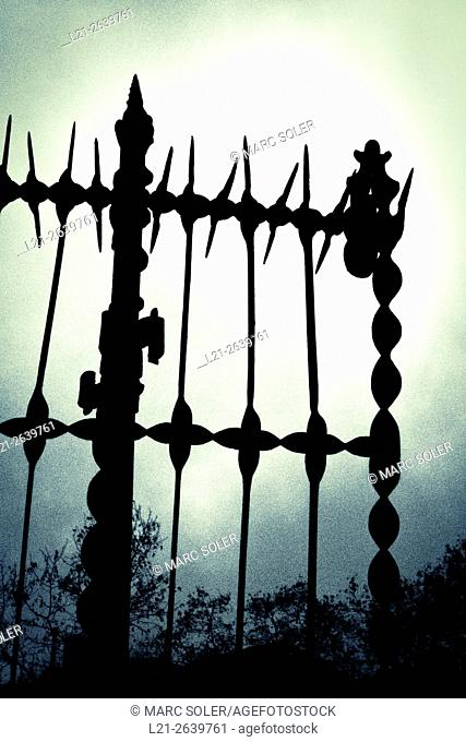 Silhouette of iron fence detail against cloudy sky