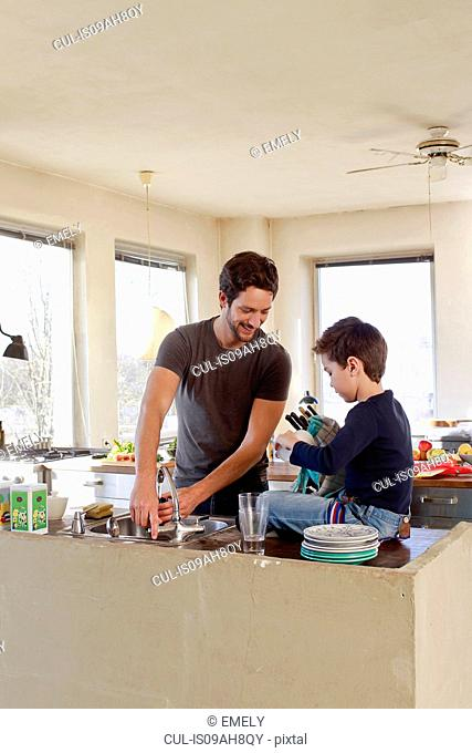 Father and young son clearing up in kitchen