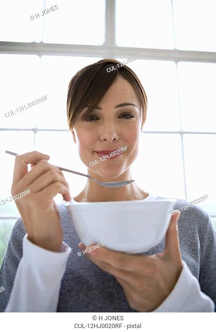 Woman holding spoon and bowl