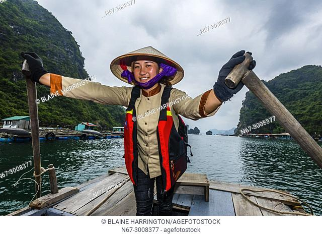 Local woman rowing a rowboat in Halong Bay, North Vietnam. The bay features 3,000 limestone and dolomite karsts and islets in various shapes and sizes sprinkled...