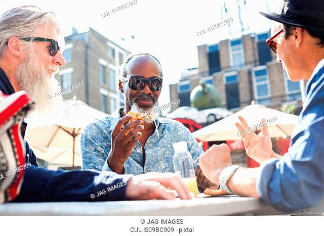 Friends having pizza at food market, London, UK