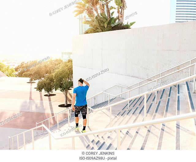 Man training, on stairway at sport facility, downtown San Diego, California, USA