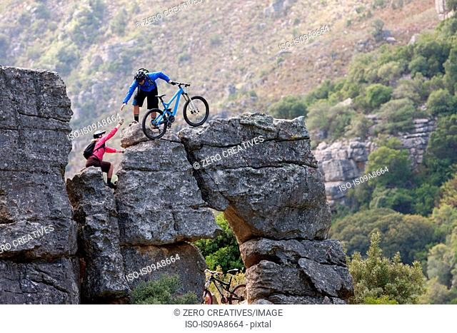 Mountain biking couple climbing rock formation
