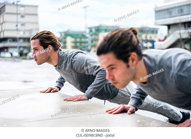 Young male twins doing push ups against wall in city