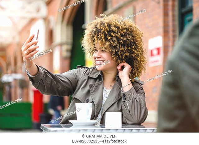 Woman taking a selfie on a smartphone. She is sat outside a cafe and is using a smart phone to take a photo