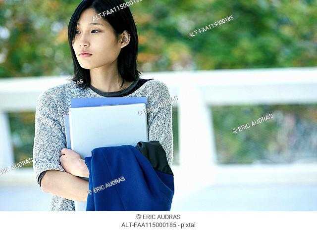 Serious woman holding laptop and file
