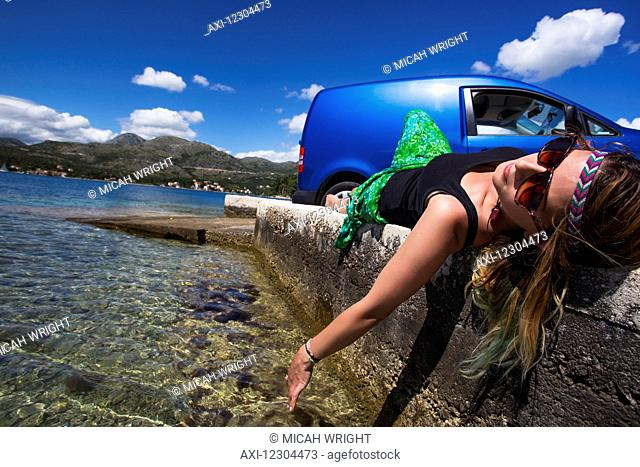 A young woman lays on a concrete wall at a beach along the coast; Slano, Croatia