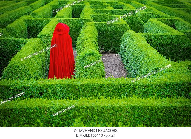 Woman in red cloak walking in hedge maze
