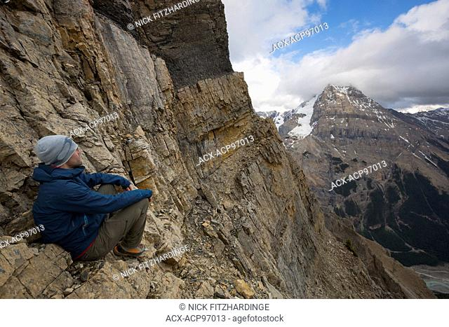 Man sitting on side of a steep mountain looking at the view of Mt Stephen, Yoho National Park, British Columbia, Canada