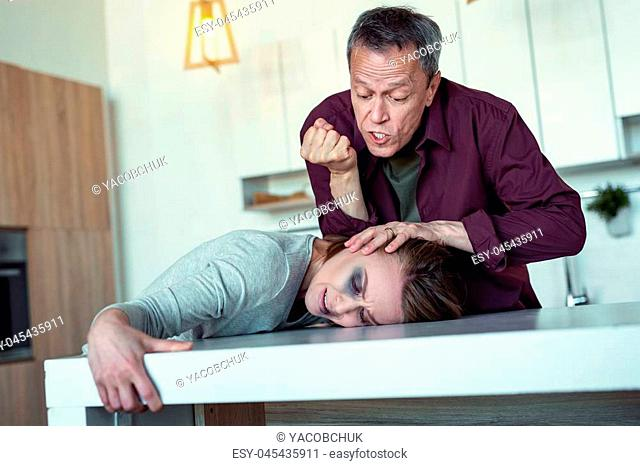 Crazy man. Crazy furious husband feeling insane while kicking his frightened wife head in the table