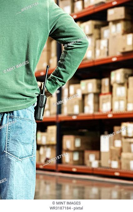 Closeup of a warehouse worker and a walkie talkie with a large rack of products in cardboard boxes in the background of a large distribution warehouse