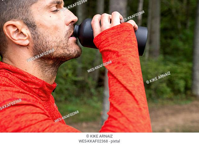 Athlete mountainbiking in nature, taking a break, drinking water