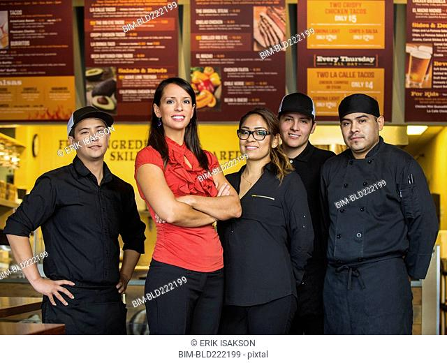 Hispanic business owner and employees smiling in cafe