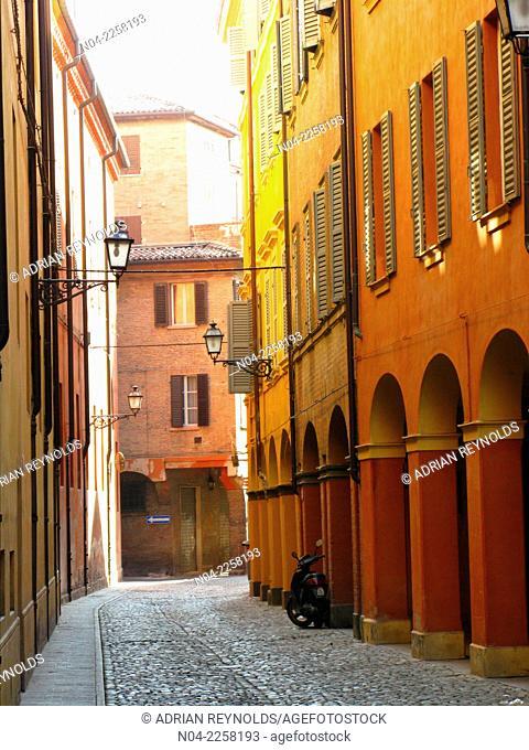 Quiet cobblestone alley with colorful buildings in Modena, Emilia-Romagna, Italy