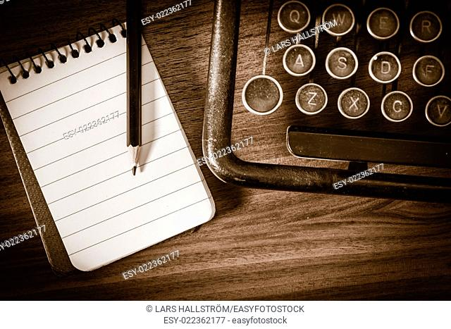 Retro vintage typewriter, pencil and notebook. Conceptual image of old fashioned office work, communication or writing