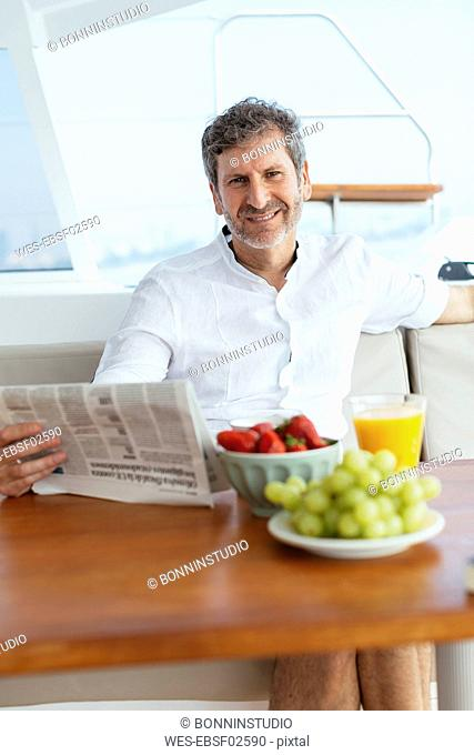 Mature man on a sailing trip having a healthy breakfast, reading newspaper