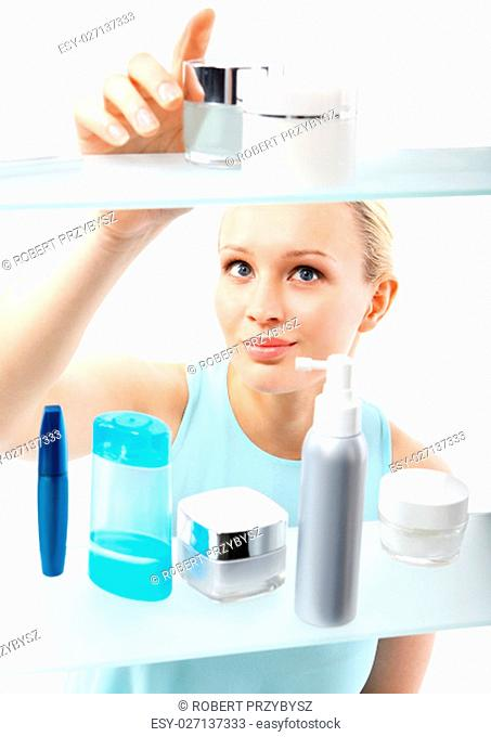 female,client standing at the shelf and selects cosmetics. woman chooses face cream. shopping in perfumery
