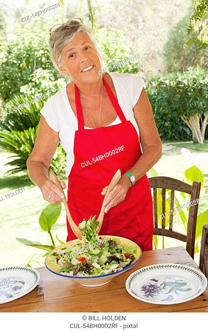 Older woman tossing salad outdoors