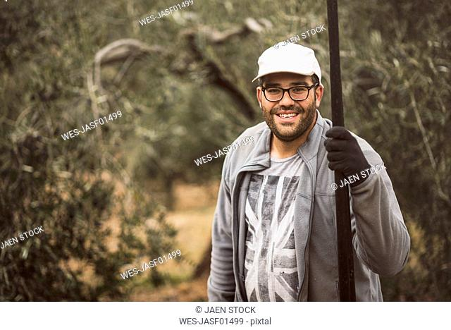 Spain, portrait of smiling worker with wooden stick in olive grove