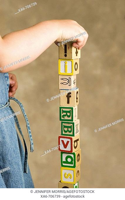A young girl stacks classic wooden letter blocks in a tall tower
