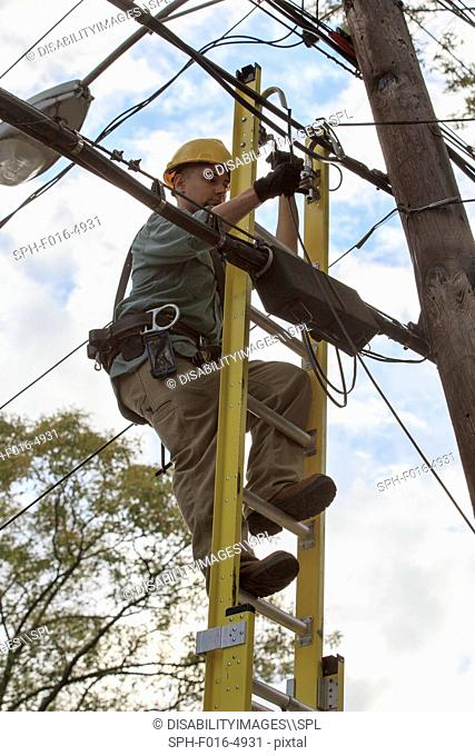 Lineman working on cables at power pole