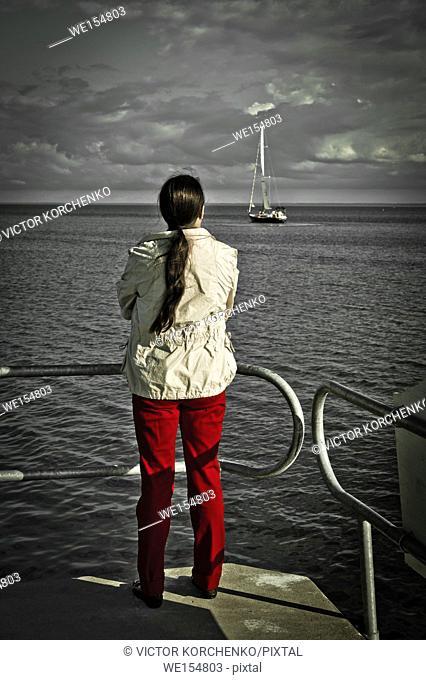 woman waching a yacht gliding on lake Ontario