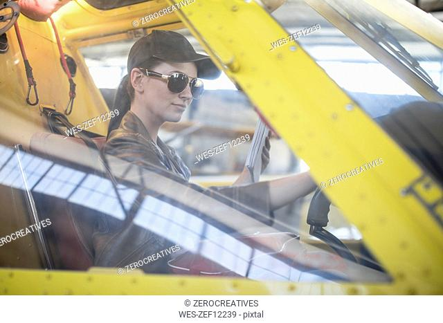 Female pilot inspecting light aircraft cockpit