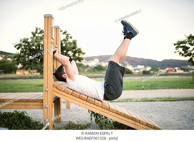 Young man doing sit-ups in a park, outdoors