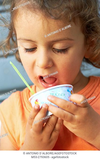 A two years old caucasian girl eating ice cream