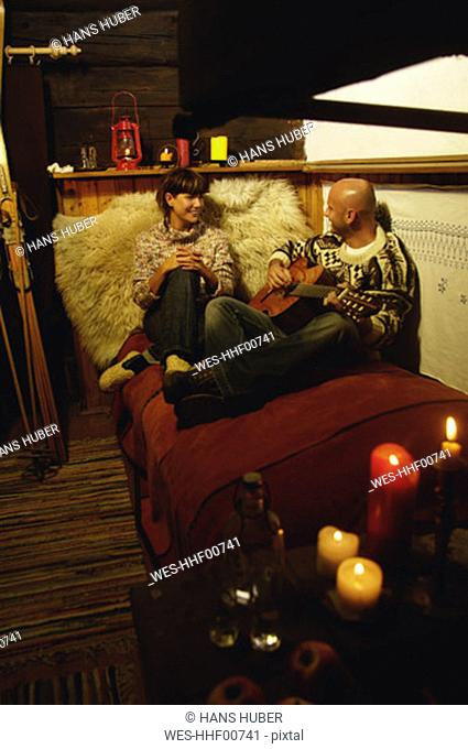 Couple sitting in bed in alpine hut, man playing guitar