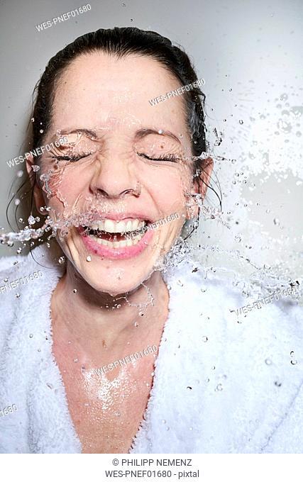 Water splashing into face of happy woman in bathrobe